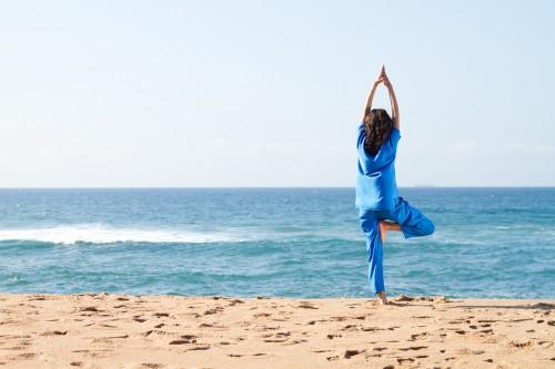 intern doing yoga on beach